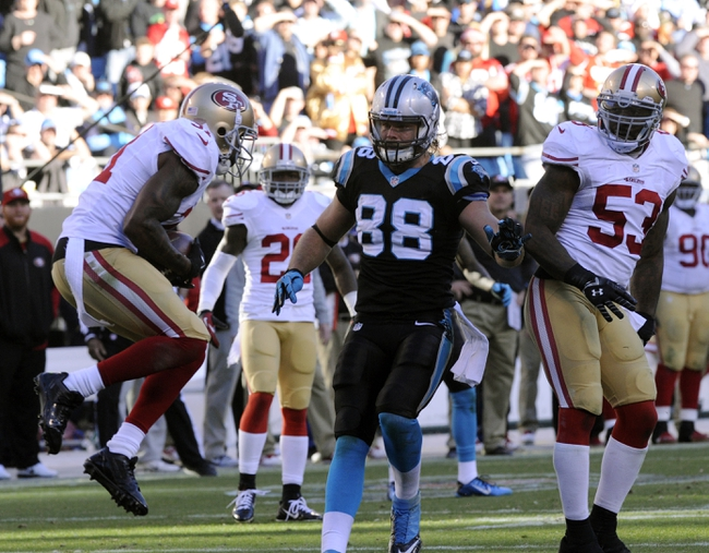Jan 12, 2014; Charlotte, NC, USA; San Francisco 49ers strong safety Donte Whitner (left) catches an interception as Carolina Panthers tight end Greg Olsen (88) watches during the fourth quarter of the 2013 NFC divisional playoff football game at Bank of America Stadium. Mandatory Credit: Sam Sharpe-USA TODAY Sports