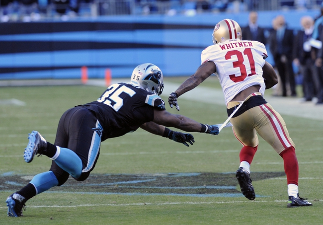 Jan 12, 2014; Charlotte, NC, USA; Carolina Panthers fullback Mike Tolbert (35) rips the pants of San Francisco 49ers strong safety Donte Whitner (31) as Whitner runs after an interception during the fourth quarter of the 2013 NFC divisional playoff football game at Bank of America Stadium. Mandatory Credit: Sam Sharpe-USA TODAY Sports