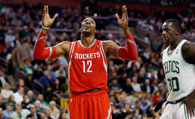 Jan 13, 2014; Boston, MA, USA; Houston Rockets power forward Dwight Howard (12) reacts while talking with a fan as Boston Celtics power forward Brandon Bass (30) looks on during the second half of Houston's 104-92 win at TD Garden. Mandatory Credit: Winslow Townson-USA TODAY Sports