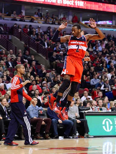 Jan 13, 2014; Chicago, IL, USA; Washington Wizards point guard John Wall (2) reacts after hitting a three point basket against the Chicago Bulls during the second half at United Center. Washington defeats Chicago 102-88. Mandatory Credit: Mike DiNovo-USA TODAY Sports