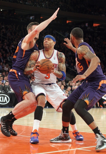 Jan 13, 2014; New York, NY, USA; New York Knicks power forward Kenyon Martin (3) drives past Phoenix Suns center Miles Plumlee (22) and Phoenix Suns power forward Marcus Morris (15) during the fourth quarter of a game at Madison Square Garden. The Knicks defeated the Suns 98-96 in overtime. Mandatory Credit: Brad Penner-USA TODAY Sports