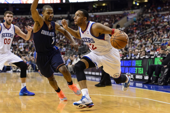 Jan 15, 2014; Philadelphia, PA, USA; Philadelphia 76ers guard Evan Turner (12) is defended by Charlotte Bobcats guard Ramon Sessions (7) during the fourth quarter at the Wells Fargo Center. The Sixers defeated the Bobcats 95-92. Mandatory Credit: Howard Smith-USA TODAY Sports