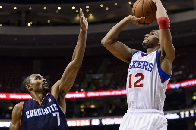 Jan 15, 2014; Philadelphia, PA, USA; Philadelphia 76ers guard Evan Turner (12) shoots a jump shot over the defense of Charlotte Bobcats guard Ramon Sessions (7) during the fourth quarter at the Wells Fargo Center. The Sixers defeated the Bobcats 95-92. Mandatory Credit: Howard Smith-USA TODAY Sports