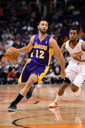 Jan 15, 2014; Phoenix, AZ, USA; Los Angeles Lakers guard Kendall Marshall (12) dribbles the ball by Phoenix Suns guard Ish Smith (3) in the first half at US Airways Center. Mandatory Credit: Jennifer Stewart-USA TODAY Sports