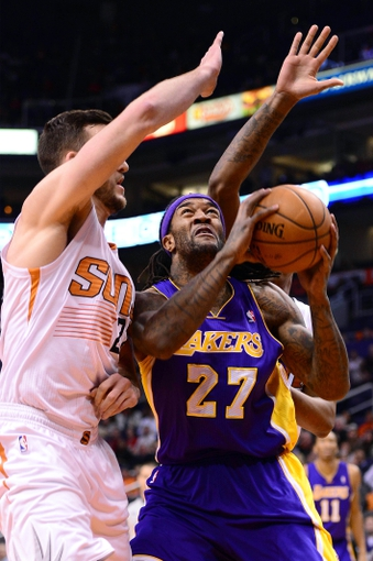 Jan 15, 2014; Phoenix, AZ, USA; Los Angeles Lakers center Jordan Hill (27) handles the ball while being defended by Phoenix Suns forward Miles Plumlee (22) in the first half at US Airways Center. The Suns won 121-114. Mandatory Credit: Jennifer Stewart-USA TODAY Sports