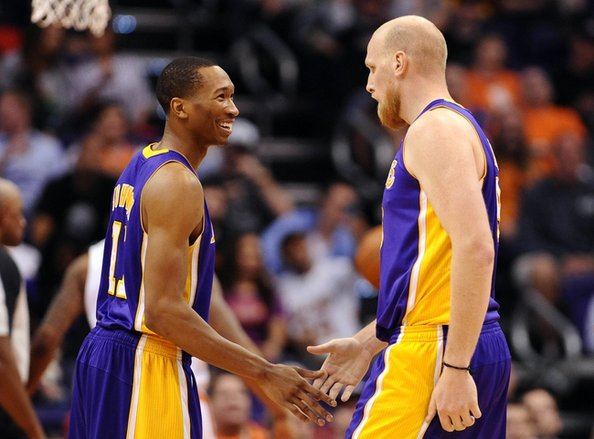 Jan 15, 2014; Phoenix, AZ, USA; Los Angeles Lakers guard Wesley Johnson (11) talks with center Chris Kaman (9) on the court against the Phoenix Suns in the second half at US Airways Center. The Suns won 121-114. Mandatory Credit: Jennifer Stewart-USA TODAY Sports