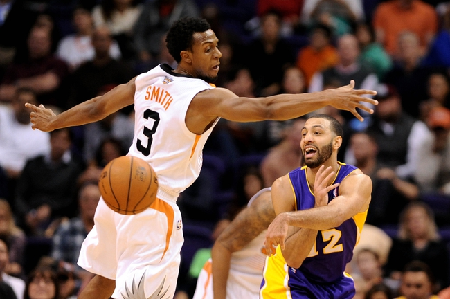 Jan 15, 2014; Phoenix, AZ, USA; Los Angeles Lakers guard Kendall Marshall (12) makes a pass around Phoenix Suns guard Ish Smith (3) in the second half at US Airways Center. The Suns won 121-114. Mandatory Credit: Jennifer Stewart-USA TODAY Sports