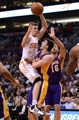 Jan 15, 2014; Phoenix, AZ, USA; Phoenix Suns guard Goran Dragic (1) commits an offensive foul against the Los Angeles Lakers forward Ryan Kelly (4) in the second half at US Airways Center. The Suns won 121-114. Mandatory Credit: Jennifer Stewart-USA TODAY Sports