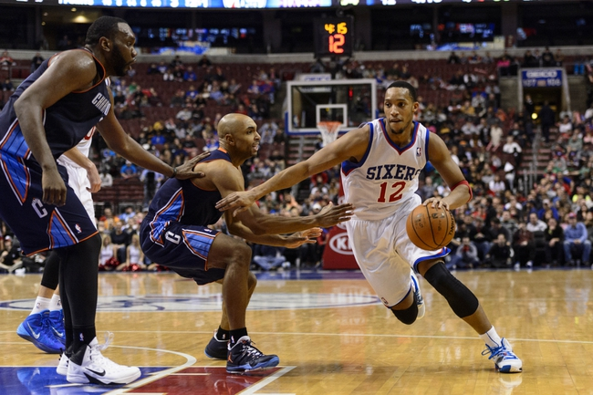 Jan 15, 2014; Philadelphia, PA, USA; Philadelphia 76ers guard Evan Turner (12) is defended by Charlotte Bobcats guard Gerald Henderson (9) and center Al Jefferson (25) during the fourth quarter at the Wells Fargo Center. The Sixers defeated the Bobcats 95-92. Mandatory Credit: Howard Smith-USA TODAY Sports