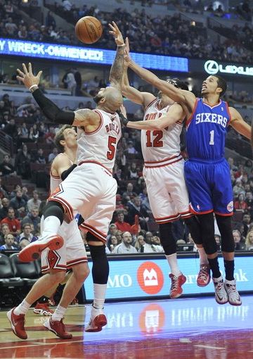Jan 18, 2014; Chicago, IL, USA;  Chicago Bulls power forward Carlos Boozer (5) and Philadelphia 76ers point guard Michael Carter-Williams (1) go up for the ball during the first quarter at the United Center. Mandatory Credit: David Banks-USA TODAY Sports
