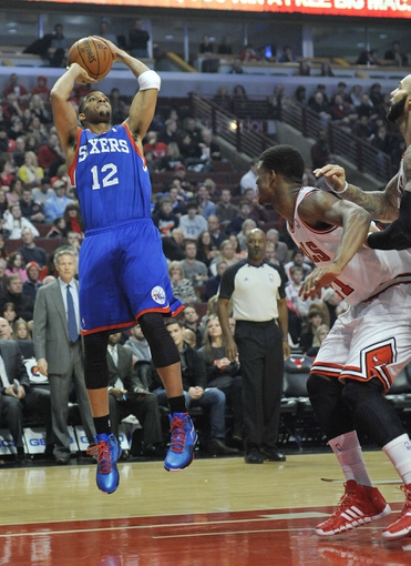 Jan 18, 2014; Chicago, IL, USA; Philadelphia 76ers small forward Evan Turner (12) shoots over Chicago Bulls shooting guard Jimmy Butler (21) during the first quarter at the United Center. Mandatory Credit: David Banks-USA TODAY Sports