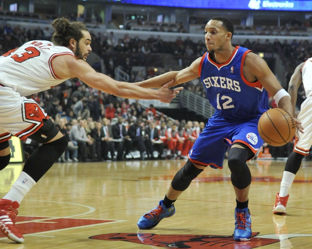 Jan 18, 2014; Chicago, IL, USA;  Philadelphia 76ers small forward Evan Turner (12) is defended by Chicago Bulls center Joakim Noah (13) during the first quarter at the United Center. Mandatory Credit: David Banks-USA TODAY Sports