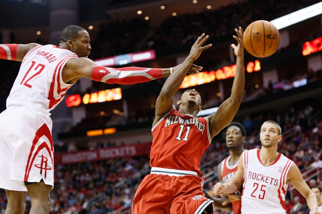 Jan 18, 2014; Houston, TX, USA; Milwaukee Bucks guard Brandon Knight (11) gets fouled while shooting against Houston Rockets center Dwight Howard (12) during the first half at Toyota Center. Mandatory Credit: Soobum Im-USA TODAY Sports