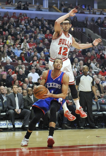 Jan 18, 2014; Chicago, IL, USA;  Chicago Bulls shooting guard Kirk Hinrich (12) defends Philadelphia 76ers point guard Michael Carter-Williams (1) during the first quarter at the United Center. Mandatory Credit: David Banks-USA TODAY Sports