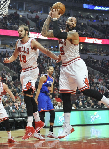 Jan 18, 2014; Chicago, IL, USA;  Chicago Bulls power forward Carlos Boozer (5) and center Joakim Noah (13) go up for a rebound against the Philadelphia 76ers during the first quarter at the United Center. Mandatory Credit: David Banks-USA TODAY Sports