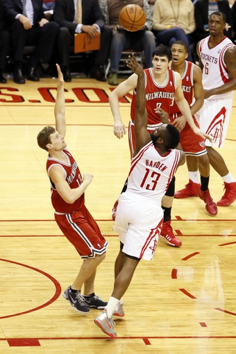 Jan 18, 2014; Houston, TX, USA; Houston Rockets guard James Harden (13) gets fouled while shooting against Milwaukee Bucks guard Luke Ridnour (left) during the first half at Toyota Center. Mandatory Credit: Soobum Im-USA TODAY Sports