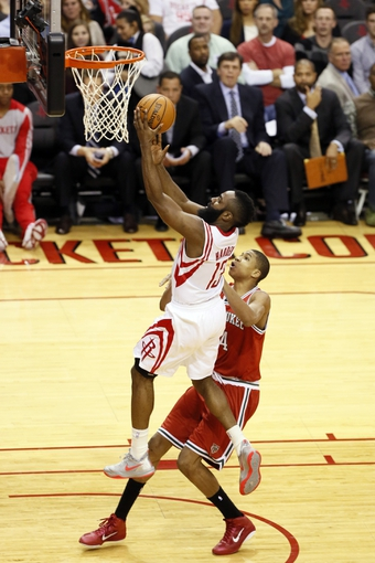 Jan 18, 2014; Houston, TX, USA; Houston Rockets guard James Harden (13) drives to the basket past Milwaukee Bucks guard Giannis Antetokounmpo (right) during the first half at Toyota Center. Mandatory Credit: Soobum Im-USA TODAY Sports