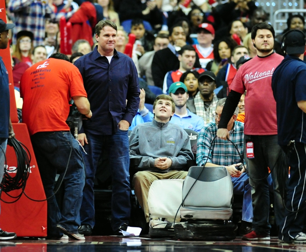 Jan 18, 2014; Washington, DC, USA; Washington Redskins head coach Jay Gruden (left) smiles at the crowd during the game between the Detroit Pistons and the Washington Wizards at Verizon Center. Mandatory Credit: Evan Habeeb-USA TODAY Sports
