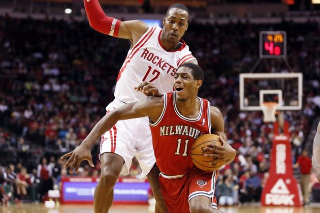 Jan 18, 2014; Houston, TX, USA; Milwaukee Bucks guard Brandon Knight (11) is fouled by Houston Rockets center Dwight Howard (12) during the second half at Toyota Center. The Rockets won 114-104. Mandatory Credit: Soobum Im-USA TODAY Sports