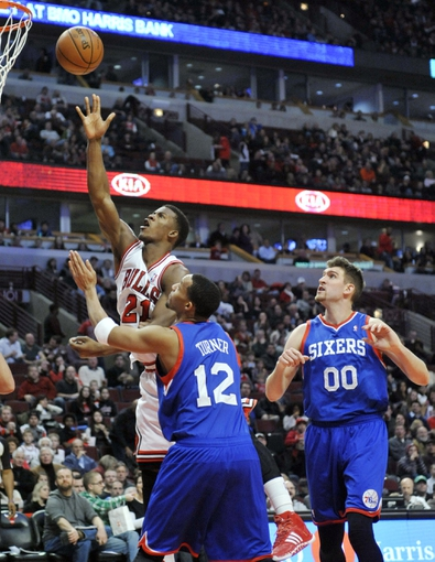 Jan 18, 2014; Chicago, IL, USA;  Chicago Bulls shooting guard Jimmy Butler (21) shoots over Philadelphia 76ers small forward Evan Turner (12) and center Spencer Hawes (00) during the second half at the United Center. The Chicago Bulls defeated the Philadelphia 76ers 103-78. Mandatory Credit: David Banks-USA TODAY Sports