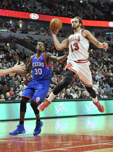 Jan 18, 2014; Chicago, IL, USA;  Chicago Bulls center Joakim Noah (13) looks to pass the ball as he's defended by Philadelphia 76ers center Dewayne Dedmon (30) during the second half at the United Center. The Chicago Bulls defeated the Philadelphia 76ers 103-78. Mandatory Credit: David Banks-USA TODAY Sports