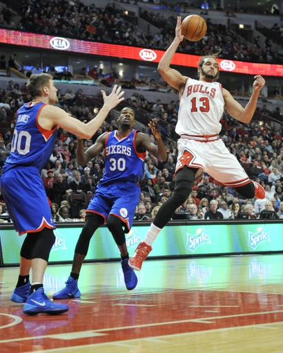 Jan 18, 2014; Chicago, IL, USA;  Chicago Bulls center Joakim Noah (13) looks to pass the ball as he's defended by Philadelphia 76ers center Dewayne Dedmon (30) and center Spencer Hawes (00) during the second half at the United Center. The Chicago Bulls defeated the Philadelphia 76ers 103-78. Mandatory Credit: David Banks-USA TODAY Sports