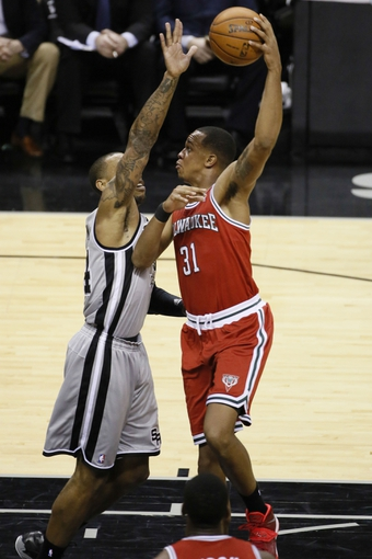 Jan 19, 2014; San Antonio, TX, USA; Milwaukee Bucks center John Henson (31) shoots against San Antonio Spurs forward Malcolm Thomas (left) during the second half at AT&T Center. The Spurs won 110-82. Mandatory Credit: Soobum Im-USA TODAY Sports