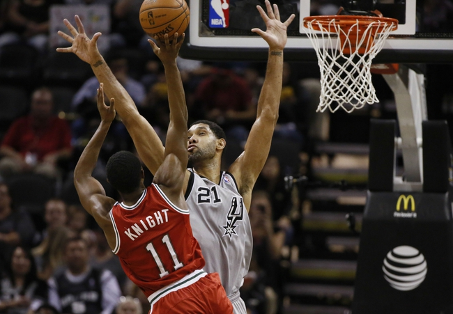 Jan 19, 2014; San Antonio, TX, USA; Milwaukee Bucks guard Brandon Knight (11) shoots while being defended by San Antonio Spurs forward Tim Duncan (21) during the first half at AT&T Center. Mandatory Credit: Soobum Im-USA TODAY Sports