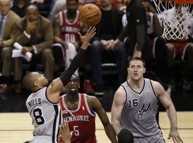 Jan 19, 2014; San Antonio, TX, USA; San Antonio Spurs guard Patrick Mills (8) drives to the basket as Milwaukee Bucks guard Nate Wolters (6) and forward Ekpe Udoh (5) look on during the second half at AT&T Center. The Spurs won 110-82. Mandatory Credit: Soobum Im-USA TODAY Sports
