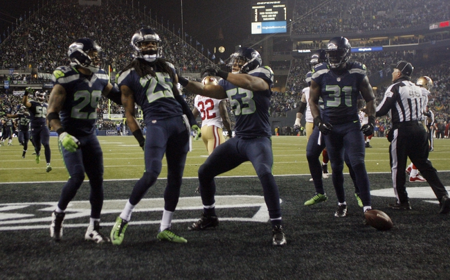 Jan 19, 2014; Seattle, WA, USA; (EDITORS NOTE: caption correction) Seattle Seahawks cornerback Richard Sherman (25) celebrates after tipping a pass to outside linebacker Malcolm Smith (53) for an interception in the fourth quarter of the 2013 NFC Championship football game against the San Francisco 49ers at CenturyLink Field. Mandatory Credit: Joe Nicholson-USA TODAY Sports