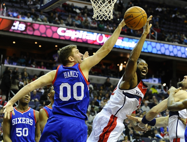Jan 20, 2014; Washington, DC, USA; Philadelphia 76ers center Spencer Hawes (00) blocks the shot attempt by Washington Wizards power forward Nene Hilario (42) during the first half at Verizon Center. Mandatory Credit: Brad Mills-USA TODAY Sports