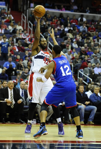 Jan 20, 2014; Washington, DC, USA; Washington Wizards power forward Nene Hilario (42) passes the ball as Philadelphia 76ers small forward Evan Turner (12) during the first half at Verizon Center. Mandatory Credit: Brad Mills-USA TODAY Sports