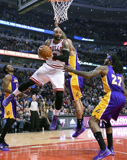 Jan 20, 2014; Chicago, IL, USA; Chicago Bulls power forward Carlos Boozer (5) grabs a rebound against Los Angeles Lakers power forward Jordan Hill (27) during the first half at United Center. Mandatory Credit: Mike DiNovo-USA TODAY Sports