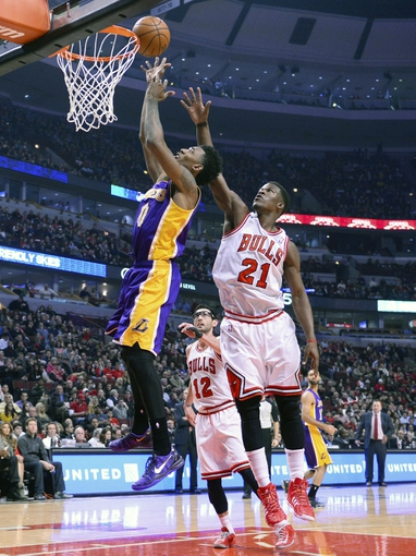 Jan 20, 2014; Chicago, IL, USA; Los Angeles Lakers small forward Nick Young (0) shoots the ball against Chicago Bulls shooting guard Jimmy Butler (21) during the first half at United Center. Mandatory Credit: Mike DiNovo-USA TODAY Sports