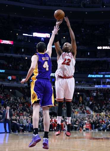 Jan 20, 2014; Chicago, IL, USA; Chicago Bulls power forward Taj Gibson (22) shoots the ball against Los Angeles Lakers power forward Ryan Kelly (4) during the second half at United Center. The Bulls defeat the Lakers 102-100 in overtime. Mandatory Credit: Mike DiNovo-USA TODAY Sports