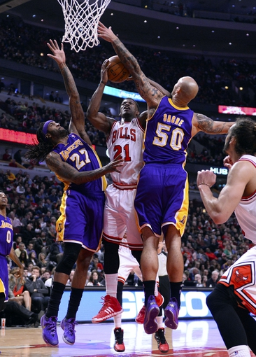 Jan 20, 2014; Chicago, IL, USA; Chicago Bulls shooting guard Jimmy Butler (21) shoots the ball against Los Angeles Lakers power forward Jordan Hill (27) and center Robert Sacre (50) during the second half at United Center. The Bulls defeat the Lakers 102-100 in overtime. Mandatory Credit: Mike DiNovo-USA TODAY Sports