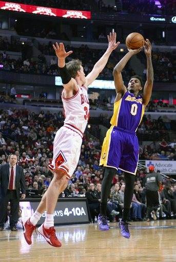 Jan 20, 2014; Chicago, IL, USA; Los Angeles Lakers small forward Nick Young (0) shoots the ball against Chicago Bulls small forward Mike Dunleavy (34) during the first half at United Center. Mandatory Credit: Mike DiNovo-USA TODAY Sports