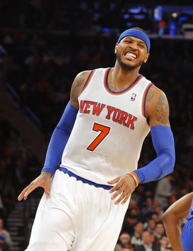 Jan 22, 2014; New York, NY, USA;  New York Knicks small forward Carmelo Anthony (7) grimaces over defeat to Philadelphia 76ers at Madison Square Garden. Philadelphia 76ers defeat the New York Knicks 110-105. Mandatory Credit: Jim O'Connor-USA TODAY Sports