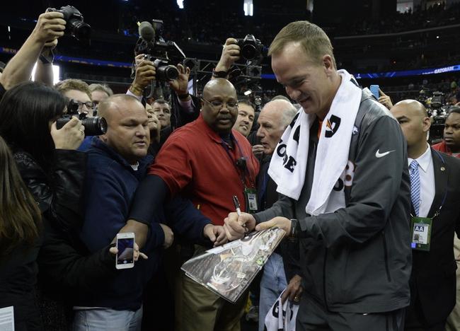 Jan 28, 2014; Newark, NJ, USA; Denver Broncos quarterback Peyton Manning signs an autograph during Media Day for Super Bowl XLVIII at Prudential Center. Mandatory Credit: Robert Deutsch-USA TODAY Sports