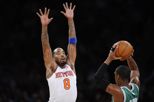 Jan 28, 2014; New York, NY, USA; New York Knicks shooting guard J.R. Smith (8) guards Boston Celtics point guard Rajon Rondo (9) during the second half at Madison Square Garden. The New York Knicks won the game 114-88. Mandatory Credit: Joe Camporeale-USA TODAY Sports