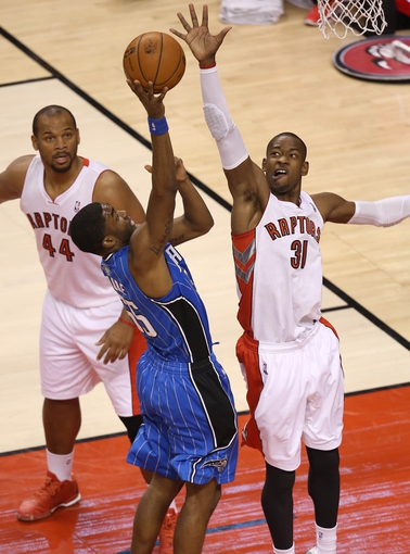 Jan 29, 2014; Toronto, Ontario, CAN; Orlando Magic guard E'Twaun Moore (55) shoots as Toronto Raptors guard Terrence Ross (31) defends at Air Canada Centre. Mandatory Credit: Tom Szczerbowski-USA TODAY Sports