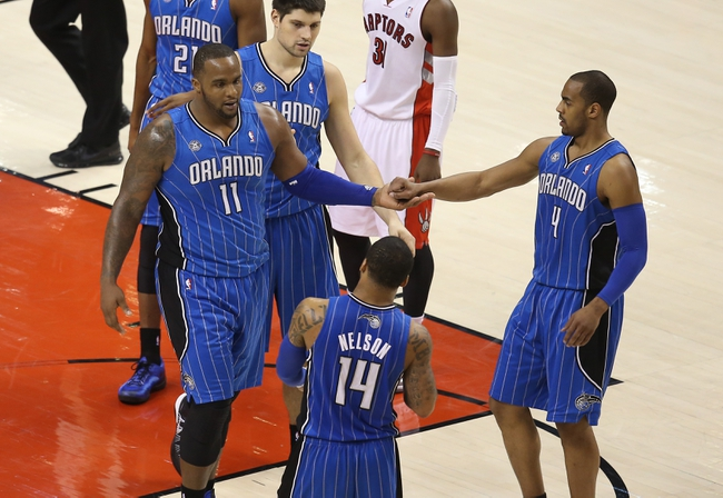 Jan 29, 2014; Toronto, Ontario, CAN; Orlando Magic forward Glen Davis (11) celebrates a basket with shooting guard Arron Afflalo (4) as center Nikola Vucevic (9) looks on against the Toronto Raptors at Air Canada Centre. The Raptors beat the Magic 98-83. Mandatory Credit: Tom Szczerbowski-USA TODAY Sports