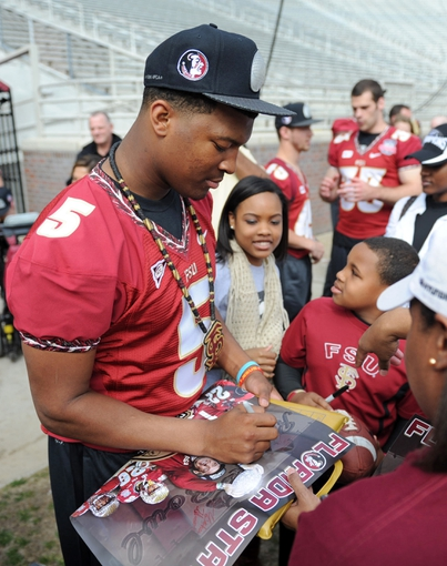 Feb 1, 2014; Tallahassee, FL, USA; Florida State Seminoles quarterback Jameis Winston (5) signs autographs during the BCS National Championship Celebration at Doak Campbell Stadium. Mandatory Credit: Melina Vastola-USA TODAY Sports
