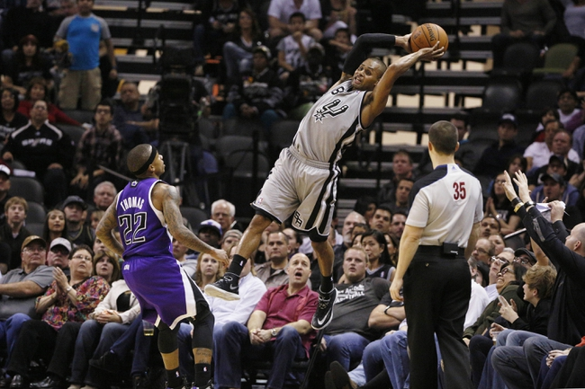 Feb 1, 2014; San Antonio, TX, USA; San Antonio Spurs guard Patrick Mills (8) reaches to save a ball from going out of bound during the second half against the Sacramento Kings at AT&T Center. The Spurs won 95-93. Mandatory Credit: Soobum Im-USA TODAY Sports