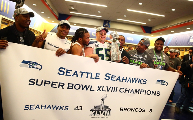 Feb 2, 2014; East Rutherford, NJ, USA; Seattle Seahawks linebacker Heath Farwell (55) holds up a banner and the Vince Lombardi Trophy in the locker room after Super Bowl XLVIII against the Denver Broncos at MetLife Stadium.  Mandatory Credit: Mark J. Rebilas-USA TODAY Sports