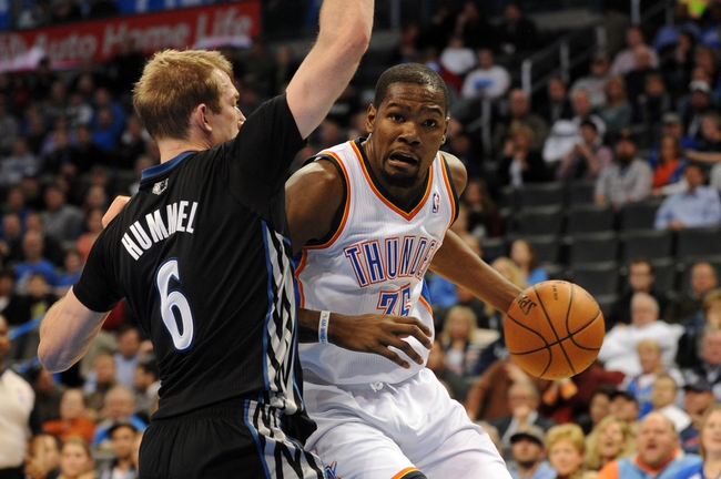 Feb 5, 2014; Oklahoma City, OK, USA; Oklahoma City Thunder small forward Kevin Durant (35) dribbles the ball around Minnesota Timberwolves small forward Robbie Hummel (6) during the fourth quarter at Chesapeake Energy Arena. Mandatory Credit: Mark D. Smith-USA TODAY Sports
