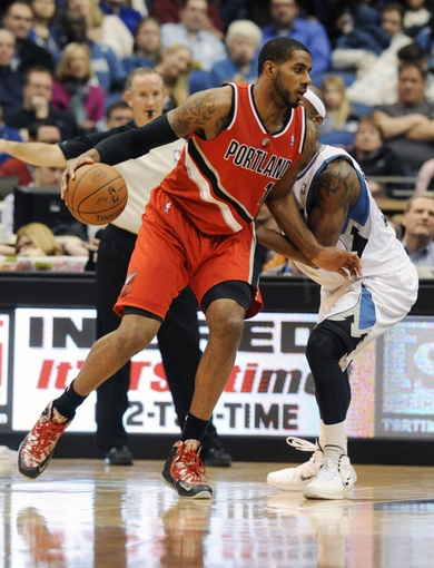 Feb 8, 2014; Minneapolis, MN, USA; Portland Trail Blazers forward LaMarcus Aldridge (12) drives around Minnesota Timberwolves forward Corey Brewer (13) in the second half at Target Center.  The Trail Blazers defeated the Wolves  117-110.  Mandatory Credit: Marilyn Indahl-USA TODAY Sports