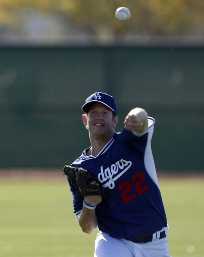 Feb 9, 2014; Glendale, AZ, USA; Los Angeles Dodgers starting pitcher Clayton Kershaw (22) warms up during the first day of camp at Camelback Ranch. Mandatory Credit: Rick Scuteri-USA TODAY Sports