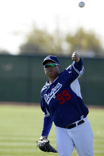 Feb 9, 2014; Glendale, AZ, USA; Los Angeles Dodgers starting pitcher Hyun-Jin Ryu (99) warms up during the first day of camp at Camelback Ranch. Mandatory Credit: Rick Scuteri-USA TODAY Sports