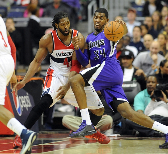 Feb 9, 2014; Washington, DC, USA; Sacramento Kings power forward Jason Thompson (34) dives to the basket as Washington Wizards power forward Nene Hilario (42) defends during the first half at Verizon Center. Mandatory Credit: Brad Mills-USA TODAY Sports